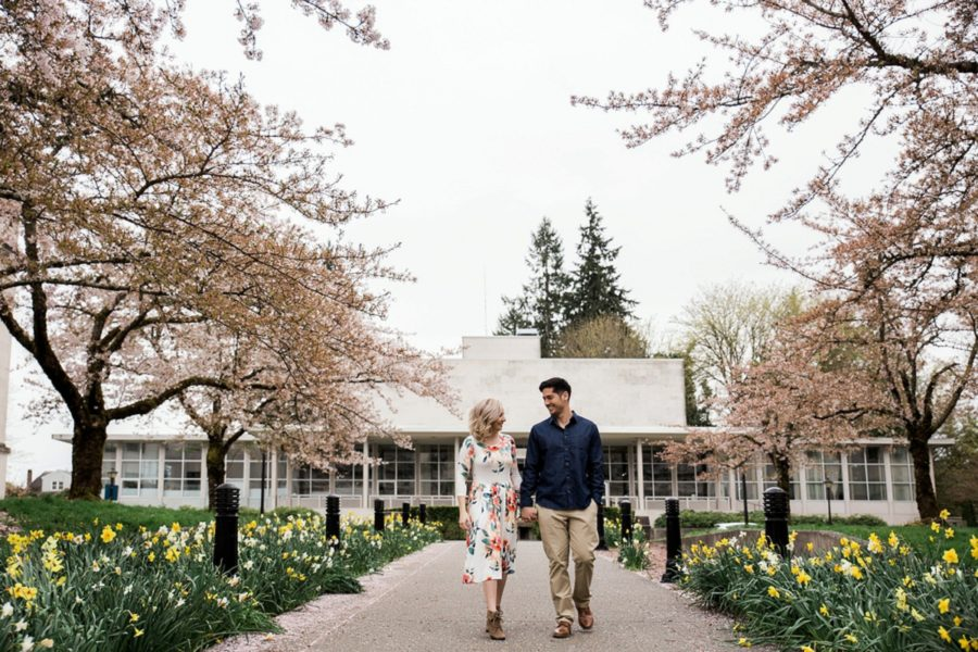 Couple walking on flower lined path, Springtime Engagement Photos in Downtown Olympia