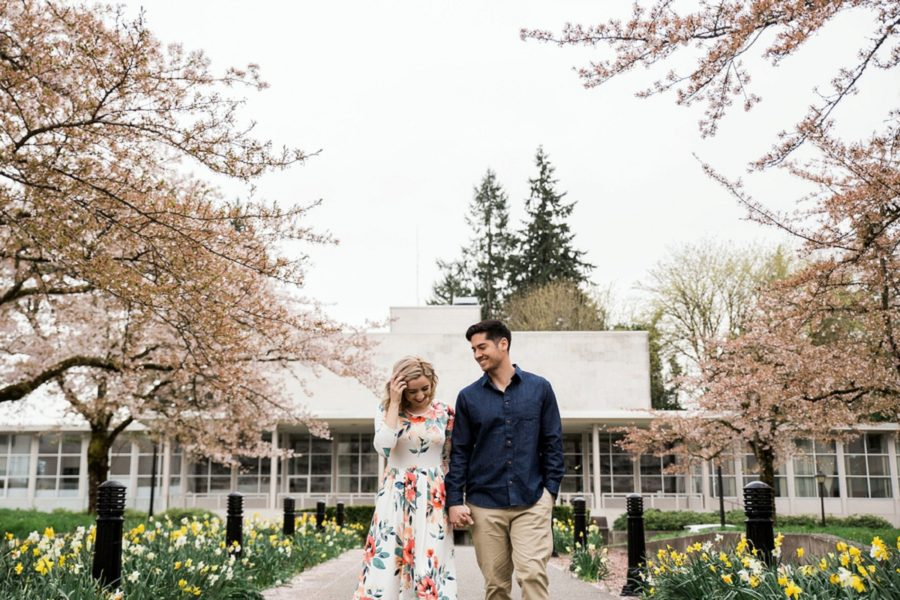 Man and woman holding hands and smiling, Springtime Engagement Photos in Downtown Olympia