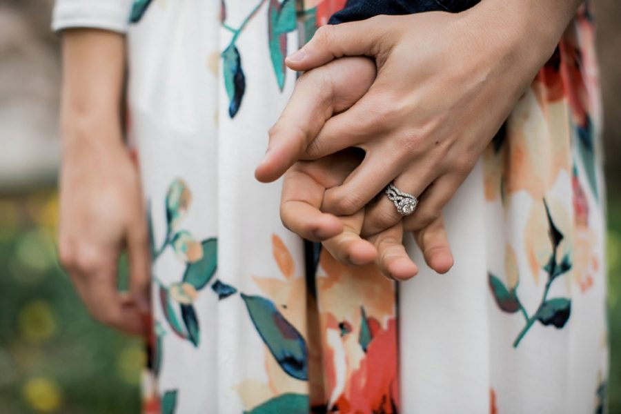 Couple holding hands, detail shot of ring on woman