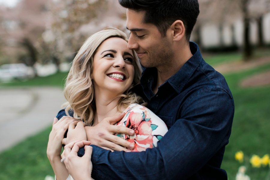 Woman smiling up at finance, Man behind woman pulling her in to embrace, Springtime Engagement Photos in Downtown Olympia