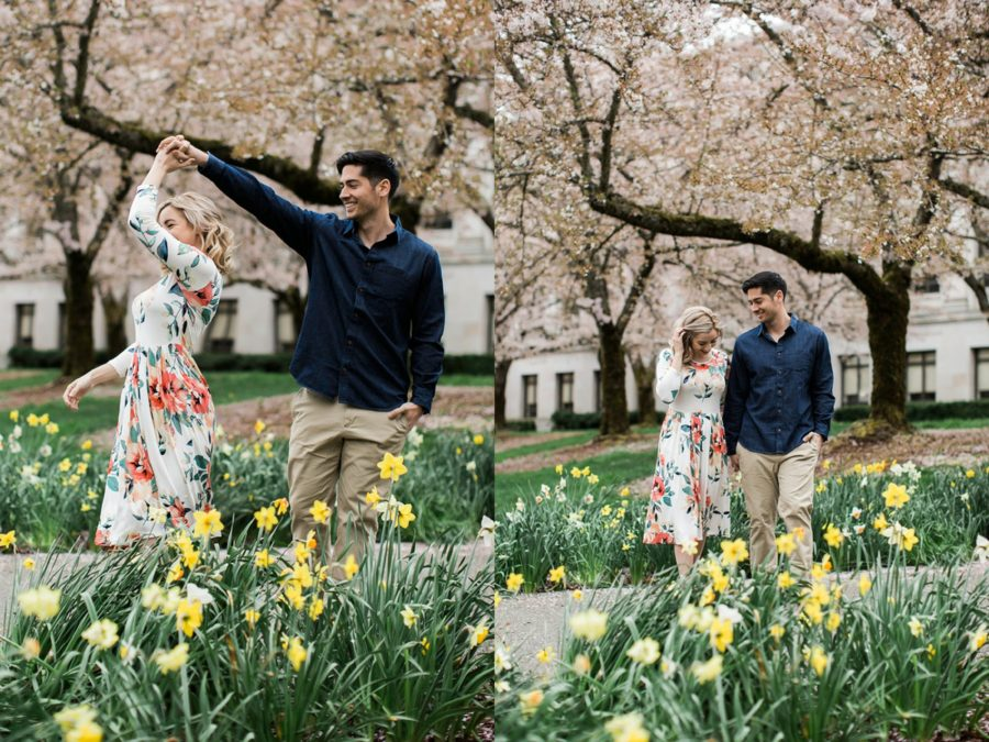 Man twirling woman under the blossoming trees, Couple dancing among the flowers, Springtime Engagement Photos in Downtown Olympia