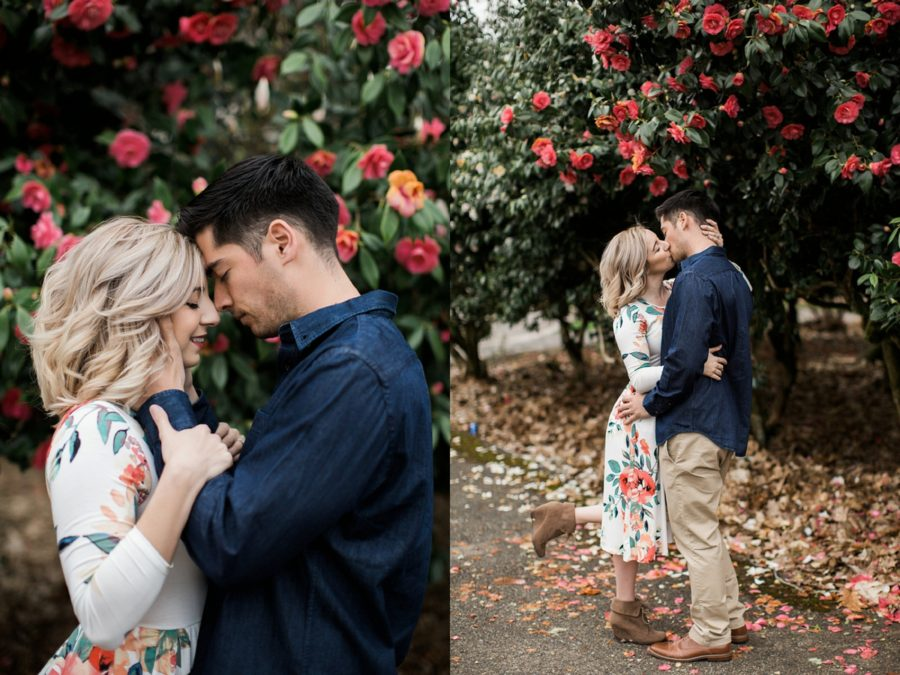 Man and woman in front of pink flowers, woman kissing man with one foot up, Springtime Engagement Photos in Downtown Olympia