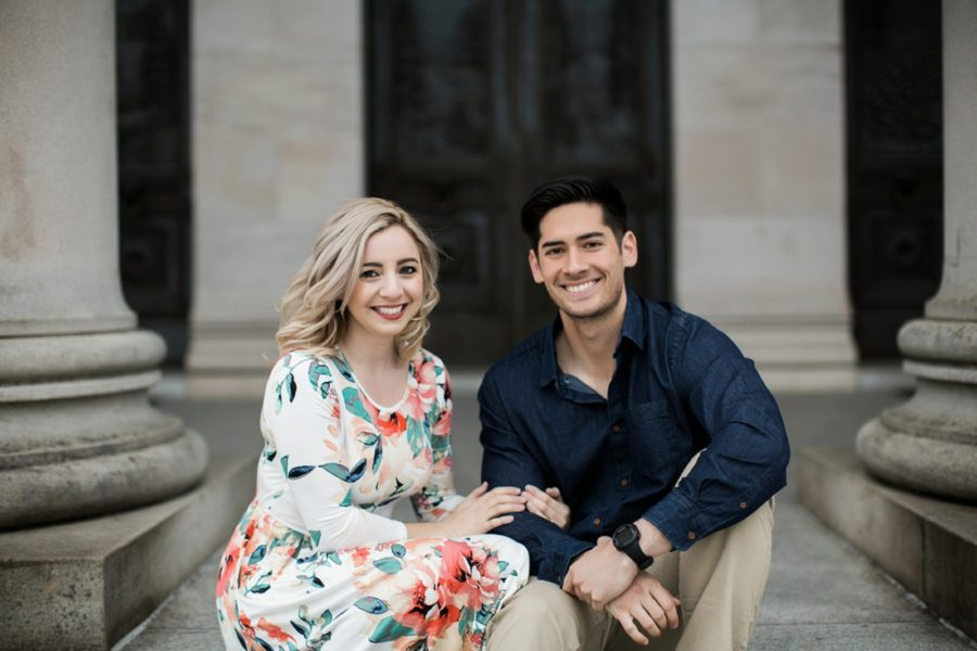 Couple smiling at camera sitting on stone steps, Springtime Engagement Photos in Downtown Olympia