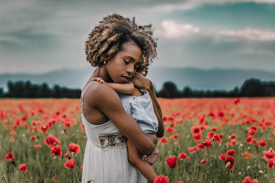 Mom snuggling child in field of poppies, Daily Fan Favorite on Beyond the Wanderlust