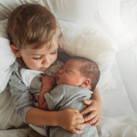 Sibling holding newborn, overhead shot of brother holding new baby, Andrea Martin Photography Daily Fan Favorite