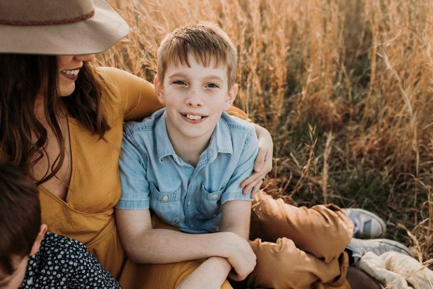 Boy smiling and mom looking at him, Outdoor Golden Hour Session with Family of 3 Boys