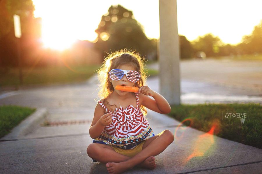 Girl in patriotic shirt and glasses eating popsicle, Daily Fan Favorite on Beyond the Wanderlust