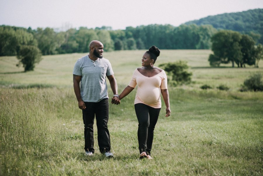Couple holding hands and walking through open field, Classy Outdoor Maternity Session in Philadelphia