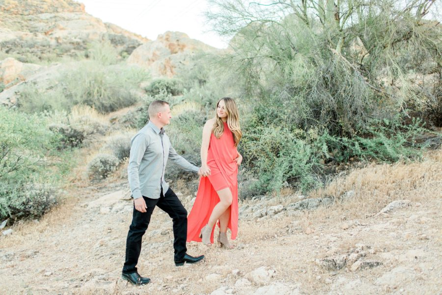 Couple holding hands and smiling at each other, Arizona desert, Canyon Lake Engagement Pictures in Arizona