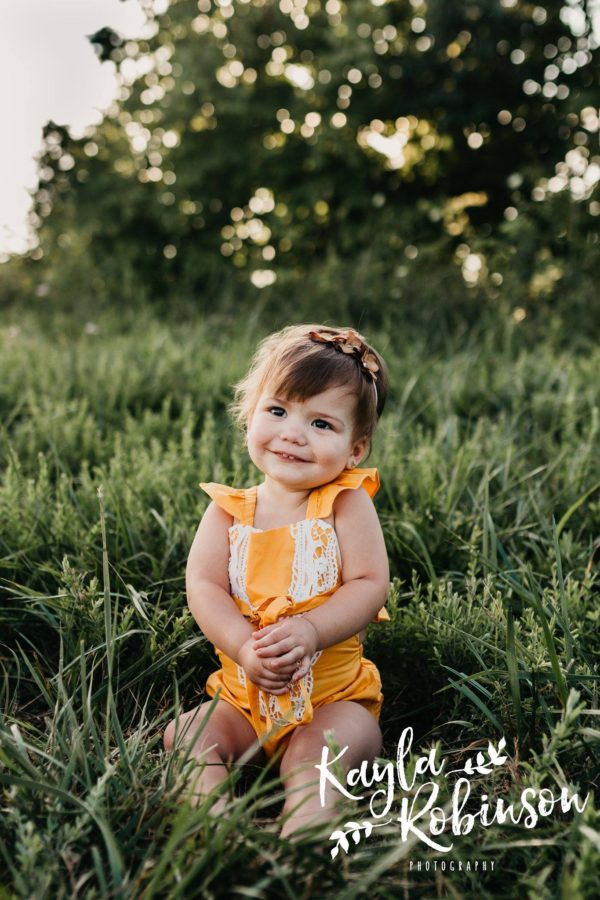 Baby smiling in grassy field, yellow vintage baby romper, Daily Fan Favorites on Beyond the Wanderlust