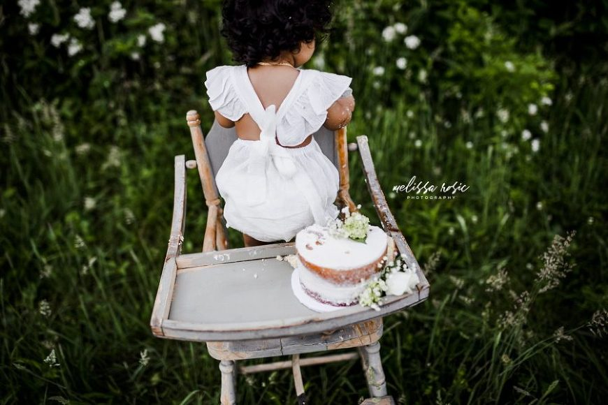Baby standing up in highchair, one year old smash cake outside, Daily Fan Favorites on Beyond the Wanderlust