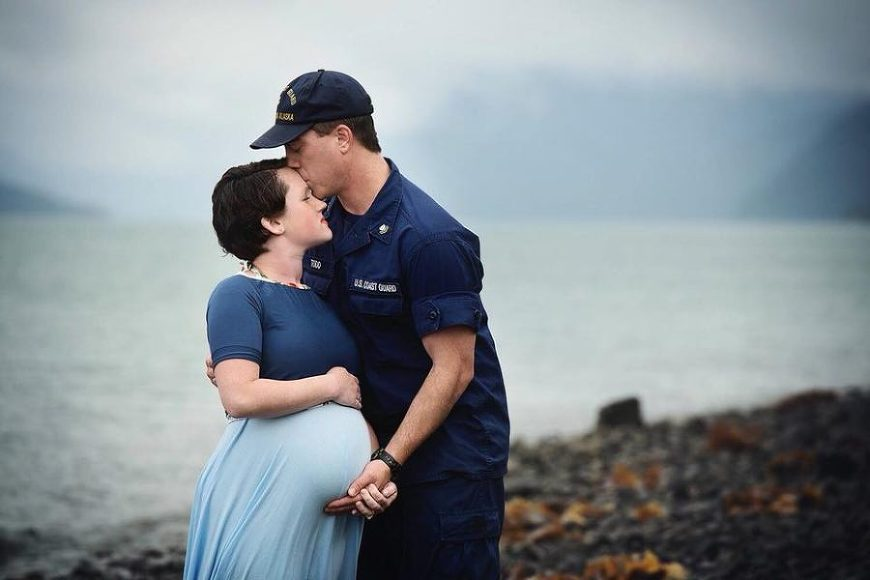 Maternity photo by the shore, Man in Navy uniform kisses pregnant wife, Daily Fan Favorites on Beyond the Wanderlust