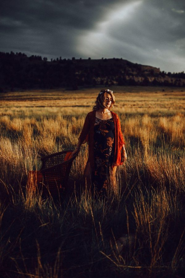 Pregnant woman standing in field under stormy sky, Daily Fan Favorite on Beyond the Wanderlust