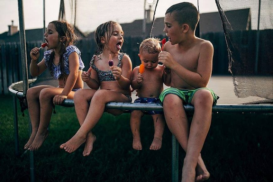 Kids sitting on edge of trampoline eating popsicles, Daily Fan Favorite on Beyond the Wanderlust