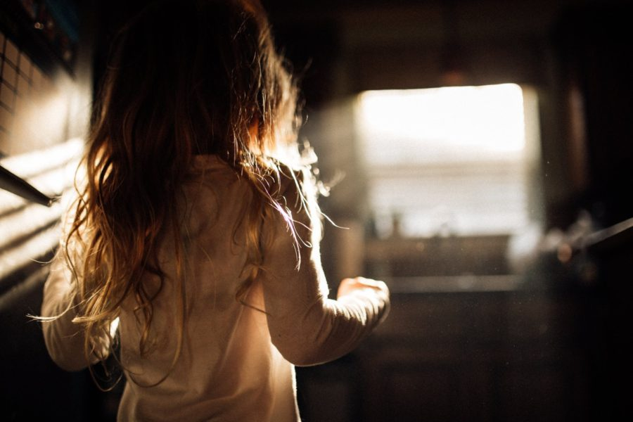 Girl standing in front of window as light streams in, Beyond the Wanderlust Daily Fan Favorites