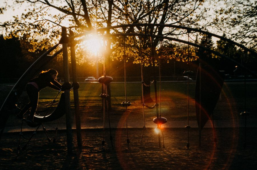 Child climbing on playground at sunset, Beyond the Wanderlust Daily Fan Favorite