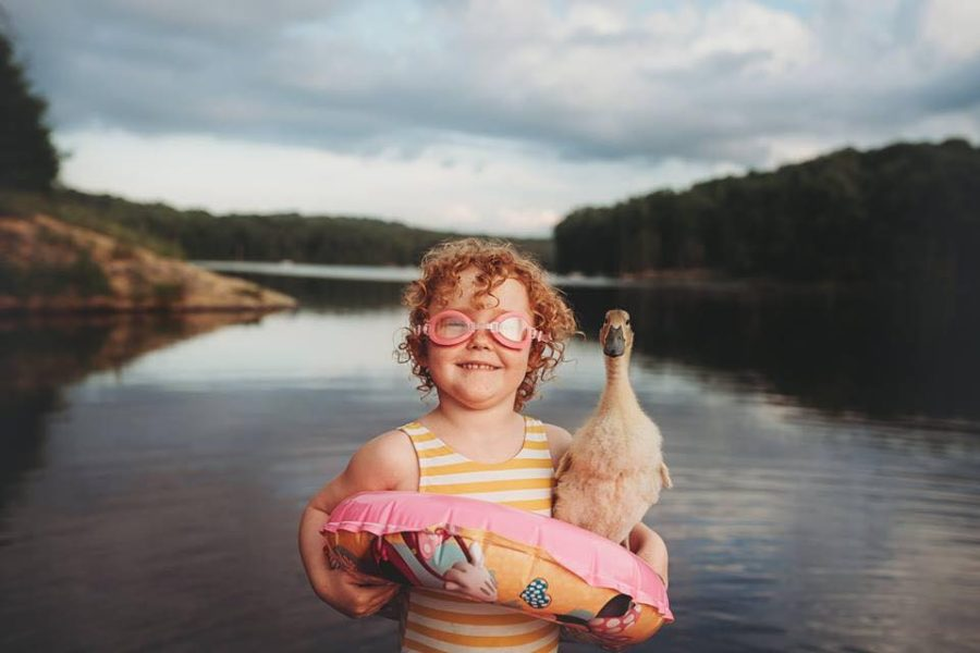 Child standing in front of lake with duck, Daily Fan Favorites on Beyond the Wanderlust