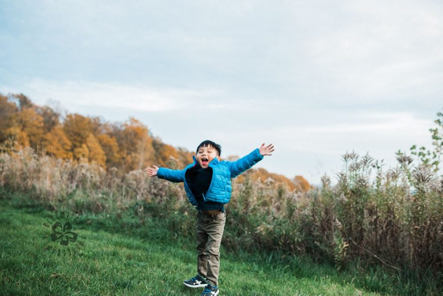 Joyful child with arms out in grass, Beyond the Wanderlust daily fan favorite