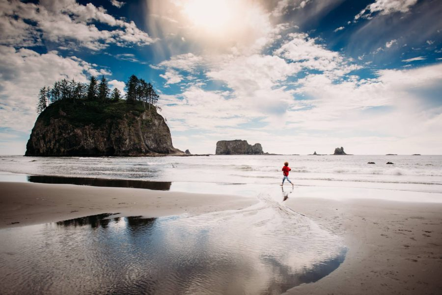 child running on coast with big rocks, Beyond the Wanderlust daily fan favorite