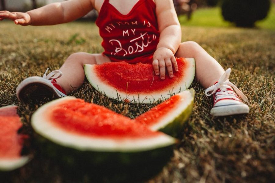 Detail shot of baby grabbing watermelon in grass, Beyond the Wanderlust Daily Fan Favorite