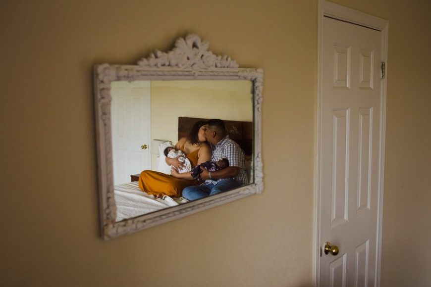Mirror reflection of family with newborns on bed, Beyond the Wanderlust Daily Fan Favorite