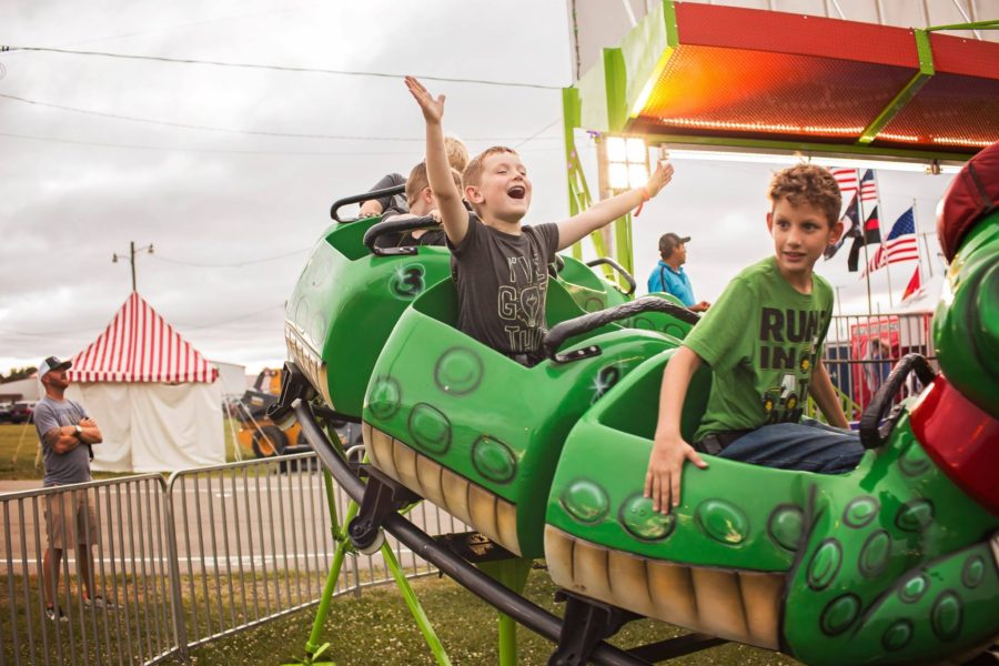 Boy holding arms up on carnival roller coaster ride, Beyond the Wanderlust Daily Fan Favorite