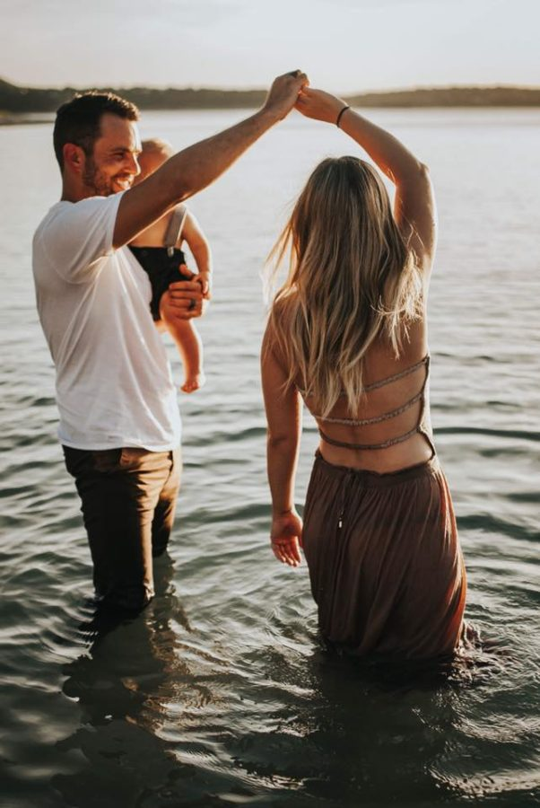 Man twirling woman in lake and holding baby, Beyond the Wanderlust Daily Fan Favorite