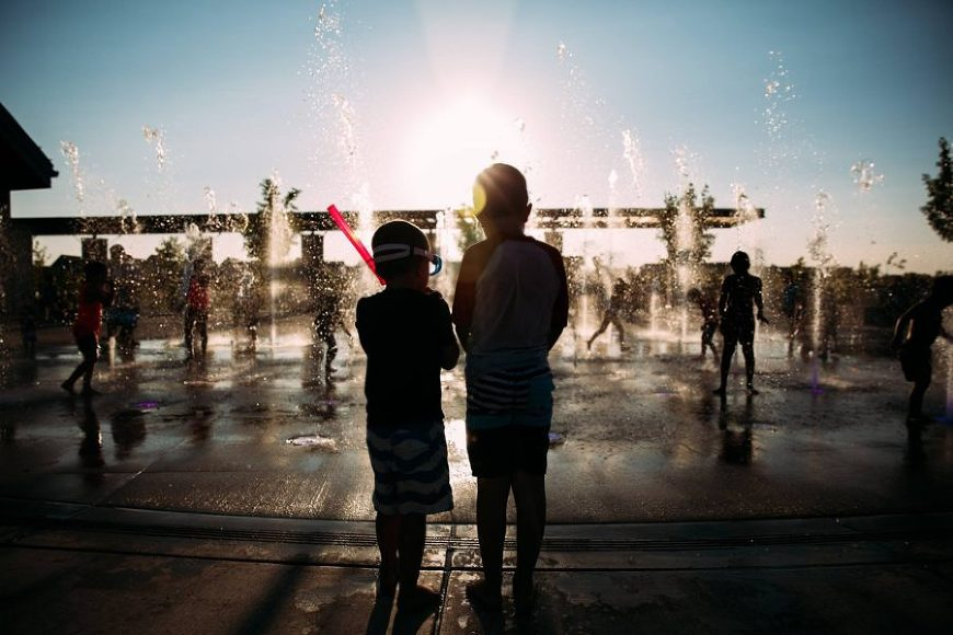 Silhouette of children in front of splash pad, Beyond the Wanderlust Daily Fan Favorite