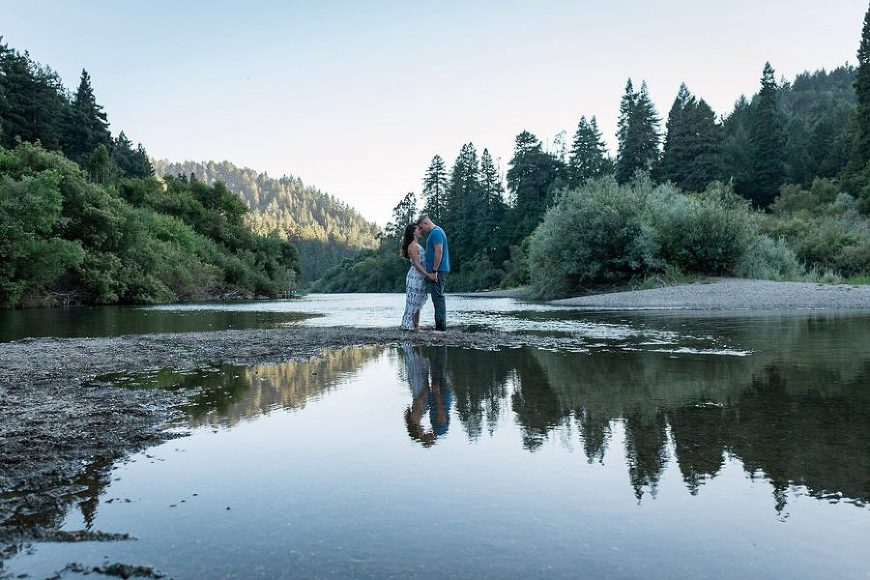 Couple standing on bank of river foreheads touching, Beyond the Wanderlust Daily Fan Favorite