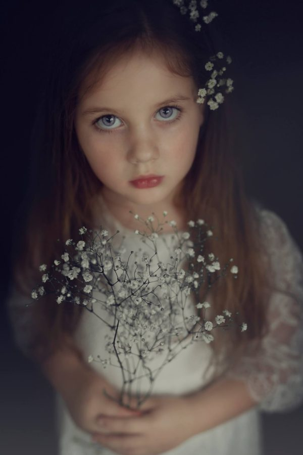 Portrait of girl looking at camera holding little white flowers, Beyond the Wanderlust Daily Fan Favorite