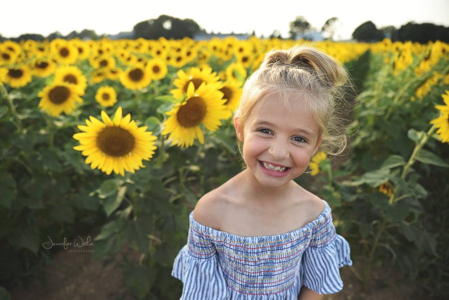 Girl smiling in front of sunflower field, Jennifer Withus Photography Daily Fan Favorite