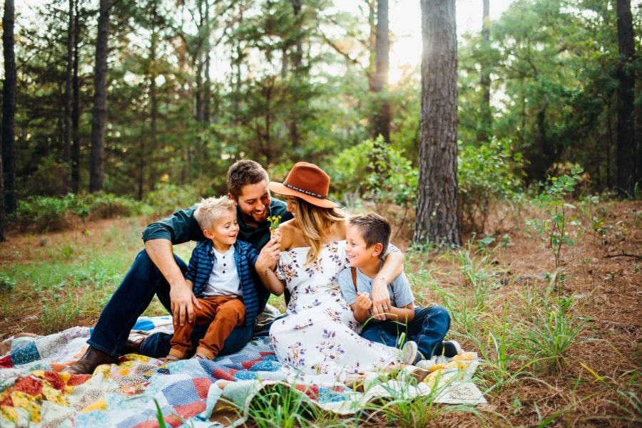 Family sitting on quilt in woods smiling, Beyond the Wanderlust Daily Fan Favorite