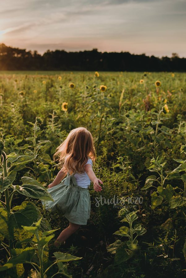 Girl twirling in sunflower field at sunset, Beyond the Wanderlust Daily Fan Favorite