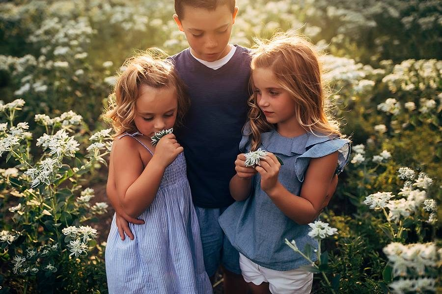Children in field of flowers together, Shelley Schuette Daily Fan Favorite