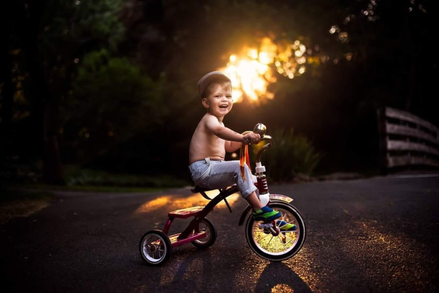 boy riding tricycle with golden light shining through trees, Beyond the Wanderlust Daily Fan Favorite