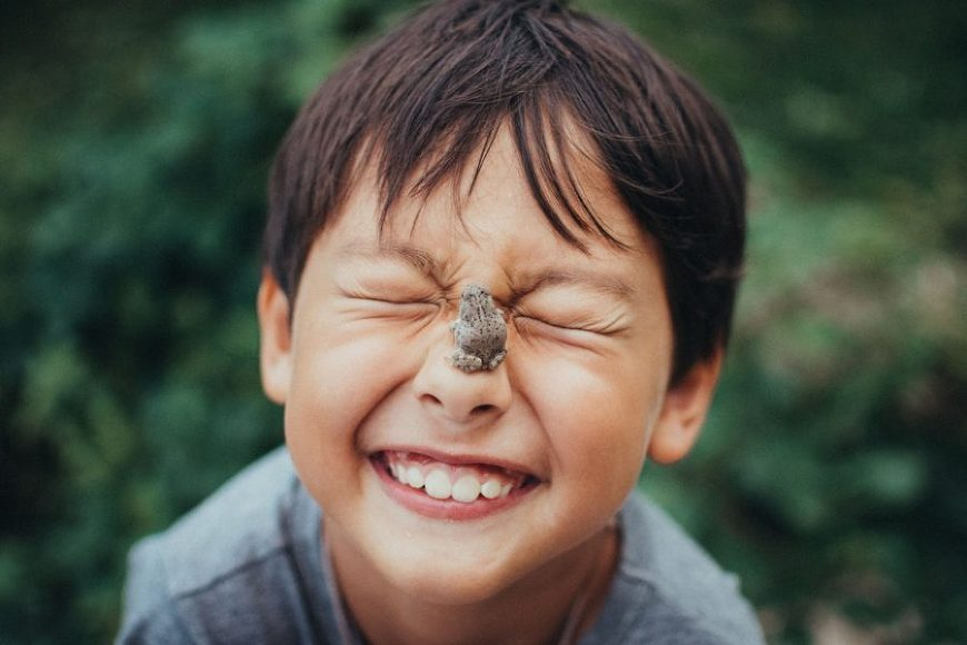 Boy smiling with frog on his nose, Beyond the Wanderlust Daily Fan Favorite