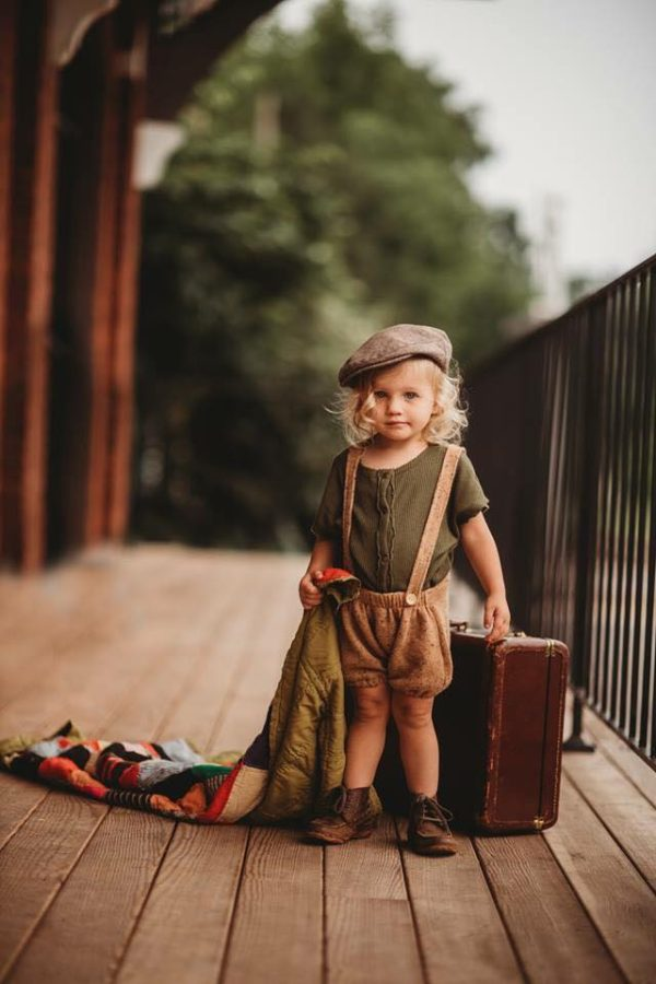 Child standing with vintage looking suitcase and outfit, Beyond the Wanderlust Daily Fan Favorite