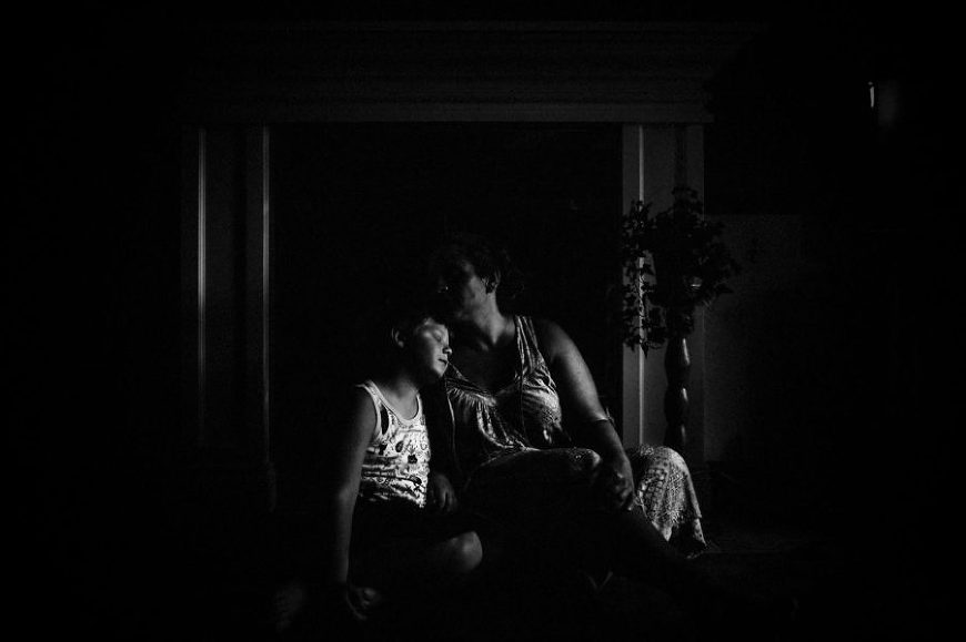 Moody image of child with head on woman