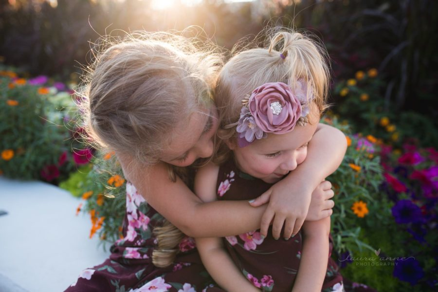 Girl with arms around younger sister in front of flowers, Beyond the Wanderlust Daily Fan Favorite