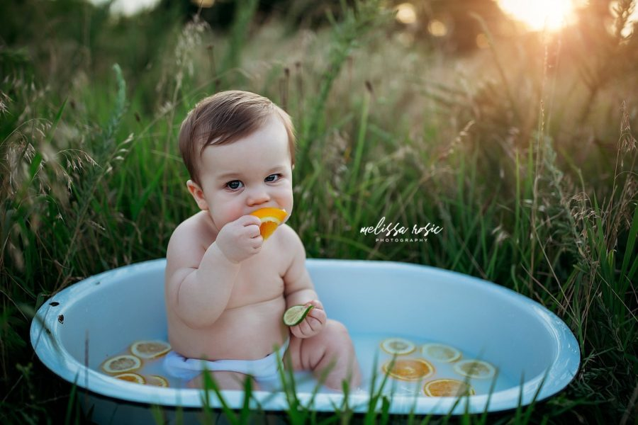 Baby in bathtub with orange slices in field, Beyond the Wanderlust Daily Fan Favorite