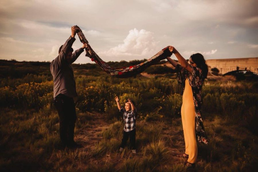Family holding blanket over child with arms up, Beyond the Wanderlust Daily Fan Favorite