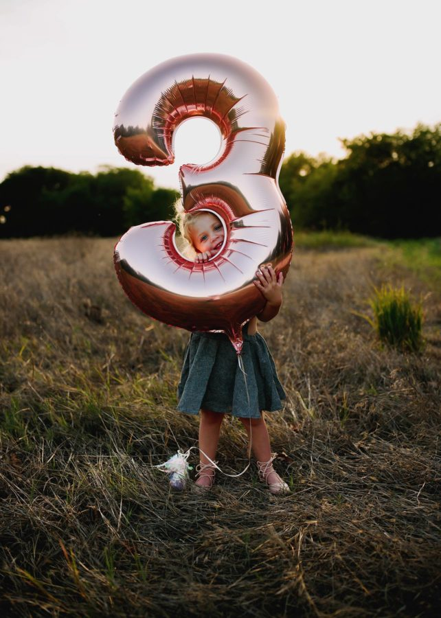 Girl holding number 3 balloon peeking through the hole, Beyond the Wanderlust Daily Fan Favorite