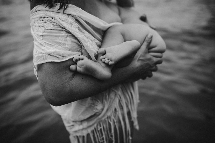 Black and white image of mother nursing baby in water, nursing photo with focus on feet in foreground, Kimberlin Photography Daily Fan Favorite