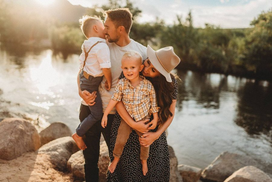 Mom and dad smiling and holding boys in front of water and sun, Beyond the Wanderlust Daily Fan Favorite
