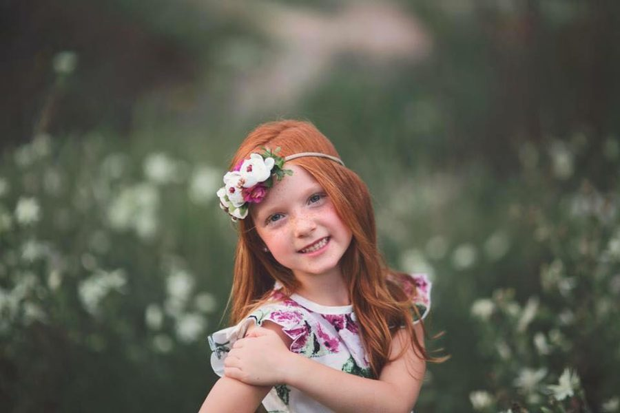 Girl smiling for photo with pink and white flower dress and headband, Kelsey Kelley Photography Daily Fan Favorite