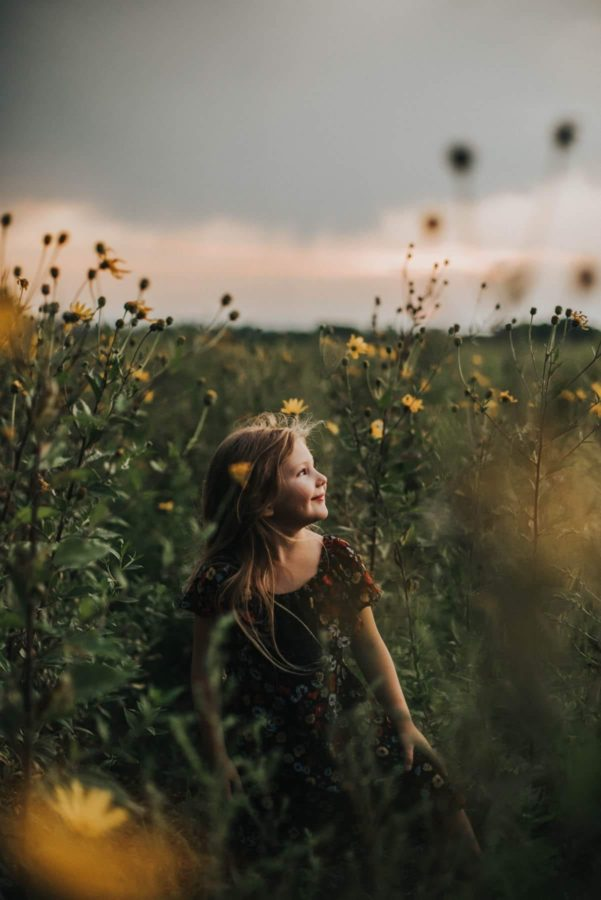 Girl walking through overgrown wildflowers face to sun, Beyond the Wanderlust Daily Fan Favorite