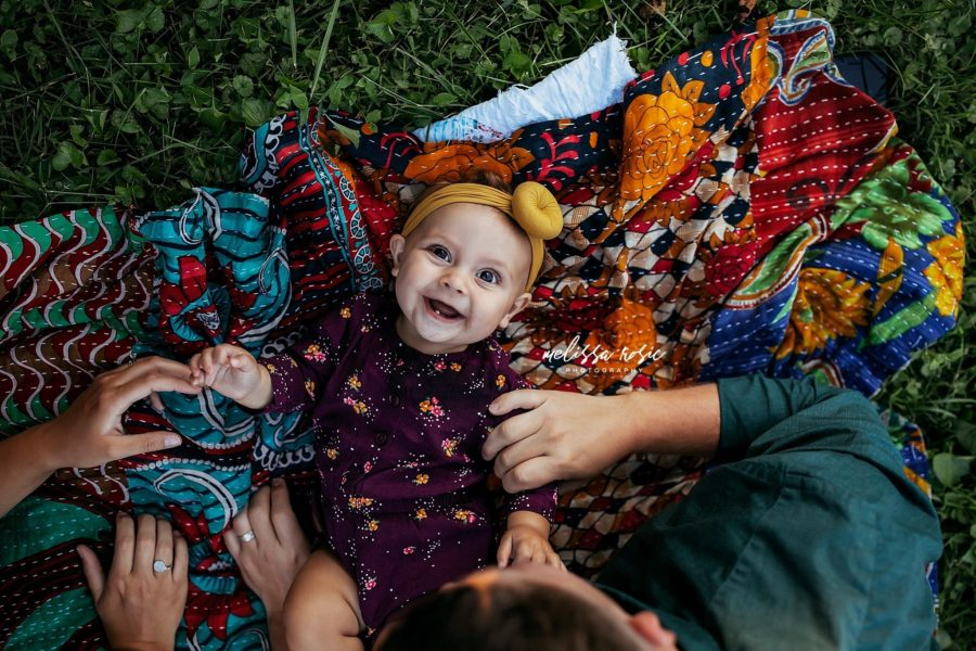Overhead photo of baby smiling on quilt parent