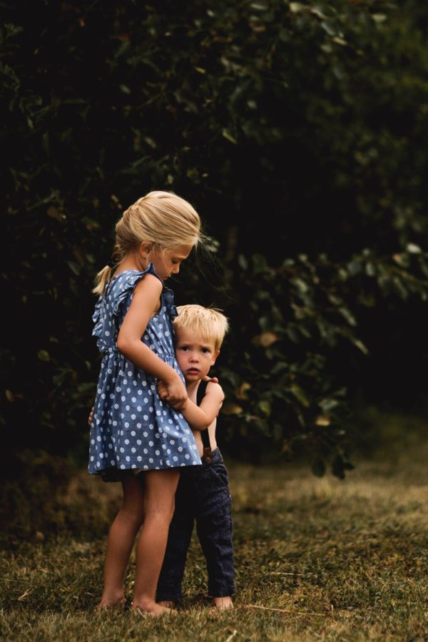Sister comforting little brother outdoors, Beyond the Wanderlust Daily Fan Favorite