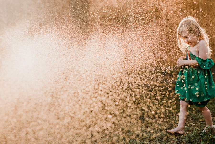 Girl walking in to golden water spray, Christina Freeman Photography Daily Fan Favorite