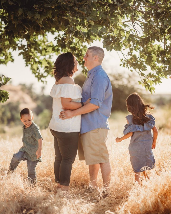 KIds running around parents as they embrace under tree, Beyond the Wanderlust Daily Fan Favorite